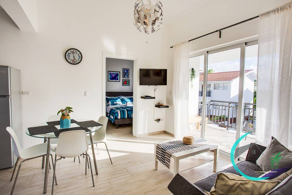 Lovely living room with dining area, sofa, Cable Tv, Balcony overlooking the residential Pool!